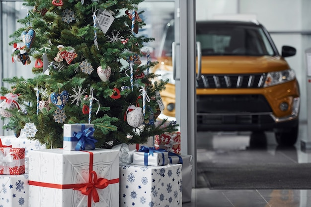 New year decorated automobile salon with christmas tree and cars