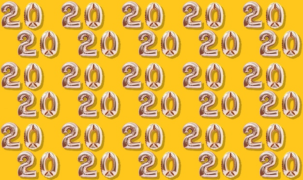 New year decoration 2020. inflatable gold numbers on the yellow background pattern.