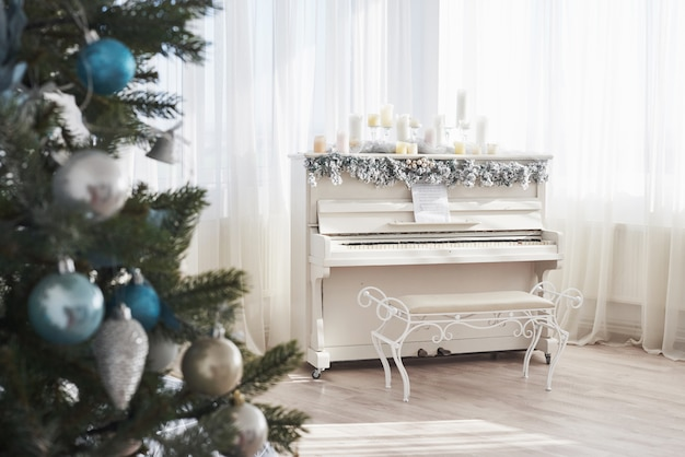 New year decoration. christmas tree near white piano at the window