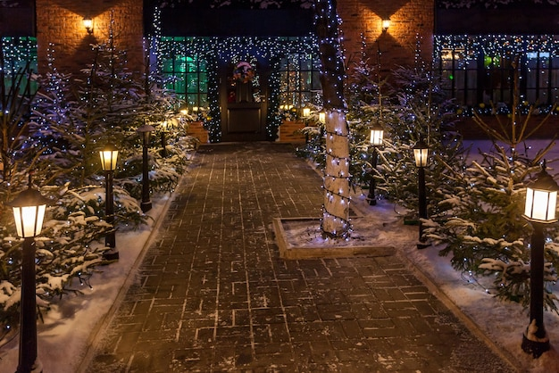 New year decoration. new year background outdoors, night view of the christmas trees, lights, garlands and gazebo with snow on the ground.