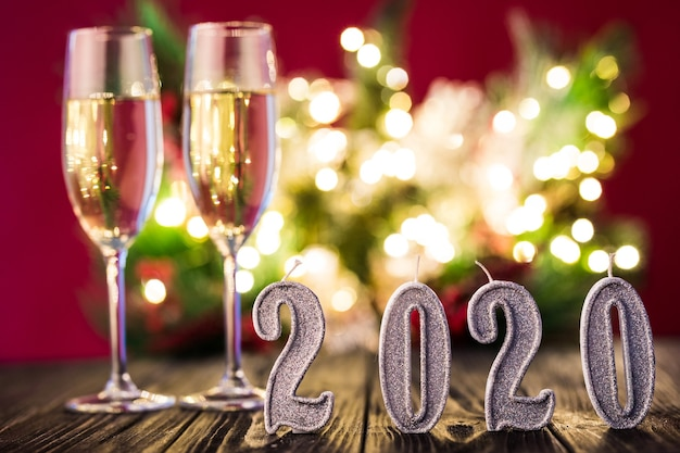 New year decoration. two gobelts with champagne with christmas or new year 2020 decoration on red light background
