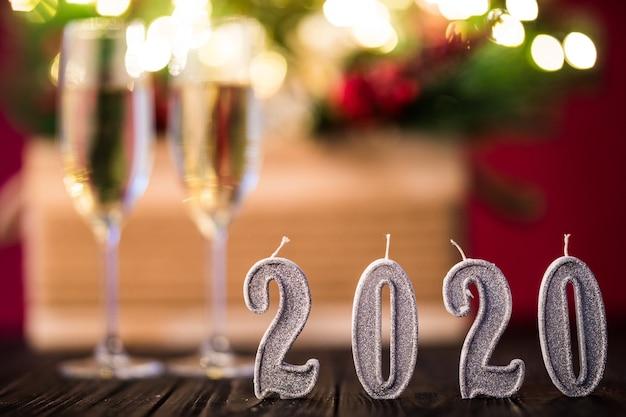 新年の飾り。赤い光の背景にクリスマスまたは新年2020の装飾が施されたシャンパンと2つのgobelts