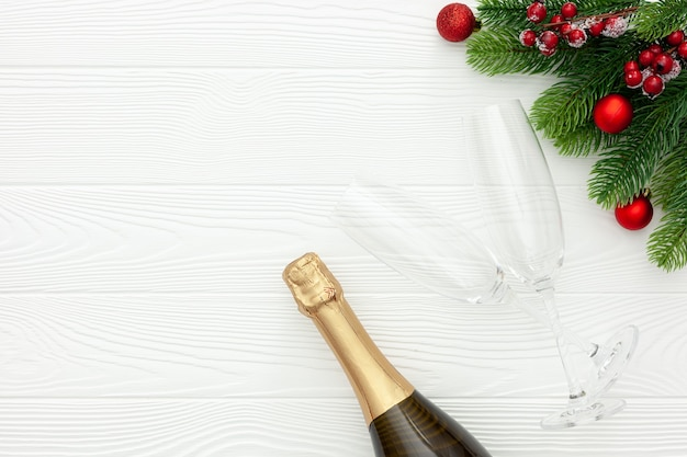 New year decoration with champagne bottle and fir branches on white wooden