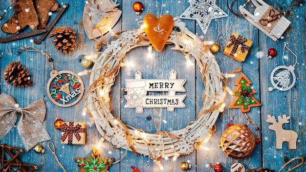青い木製の背景にテキスト燃焼ライト花輪のためのクリスマスの手紙の空きスペースの周りの新年の装飾