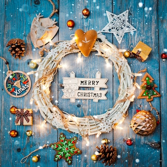 New year decorations around christmas letter empty space for text burning lights garlands on blue wooden background.