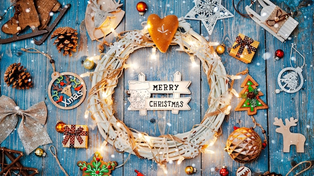 New year decorations around christmas letter empty space for text burning lights garlands on blue wooden background