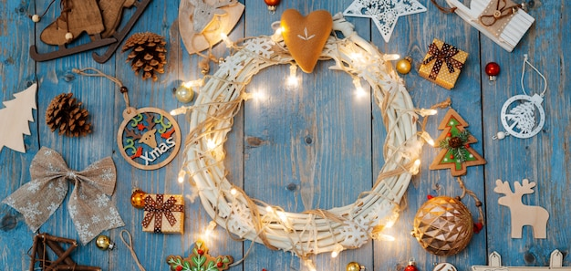 New year decorations around christmas wreath on blue wooden background.