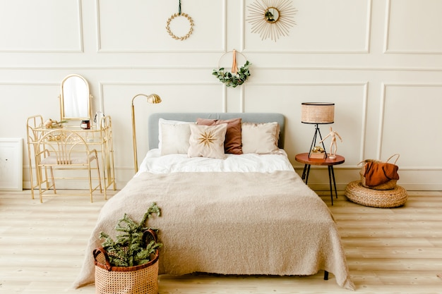 New year design interior of beautiful bedroom in beige tones with wreath spruce branches