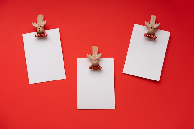 New year empty greeting cards mockups on a clothespin on a red space for text new year