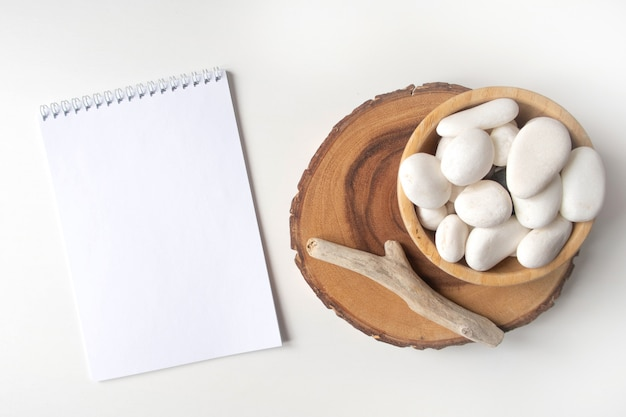 New year empty notebook list with a bowl of white pebble anf boho rustic decorations on a white tabe. mockup with copy space for your image or text