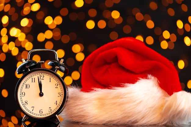New year eve concept with alarm clock against blurred garland