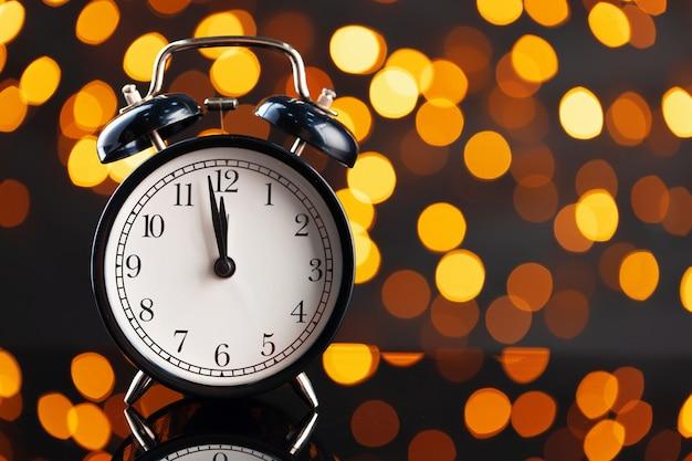 Концепция кануна нового года с будильником на фоне размытой гирлянды