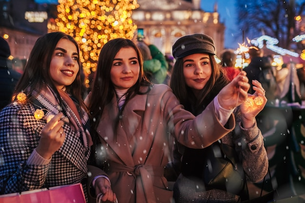 New year eve. women friends burning sparklers in lviv by christmas tree on street fair celebrating holidays. happy girls having fun under snow. party
