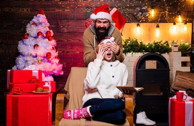Новогодняя семья с рождественским подарком перед елкой рождественский интерьерный портрет о ...