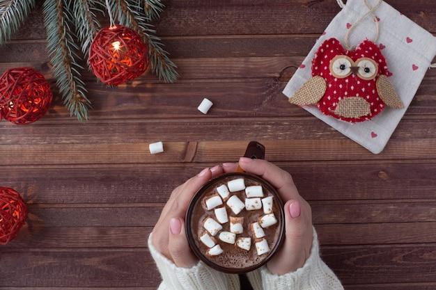 Новогодняя планировка квартиры. фон с рождественским подарком, женские руки держат чашку какао, еловые ветки и красные огни
