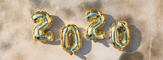 New year flat lay composition. foil balloons in the form of numbers 2020.