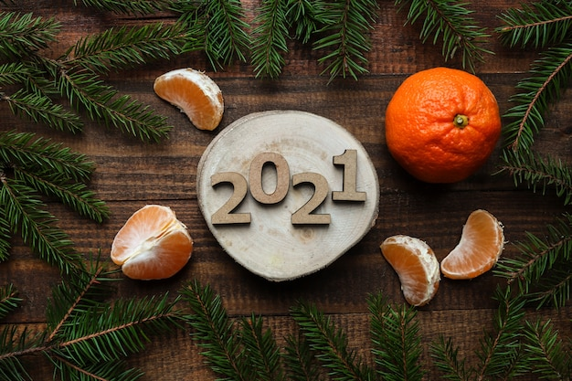 新年のフラットは、木製の番号2021、クリスマスと木製の背景にみかんで横たわっていた。