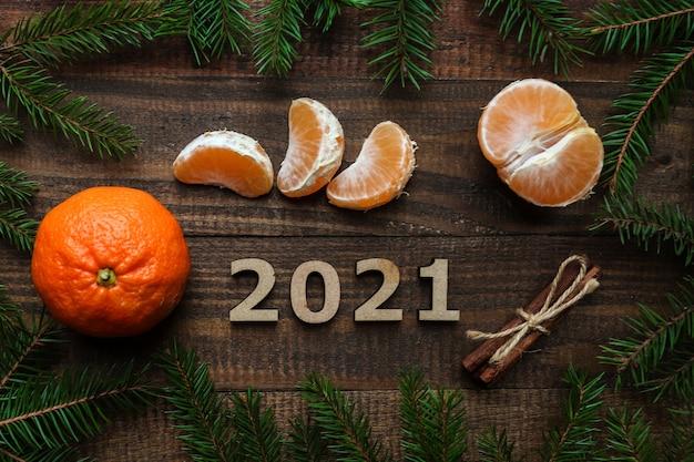 新年のフラットは、木製の数字2021、クリスマスツリー、みかん、シナモンスティックで横たわっていました。