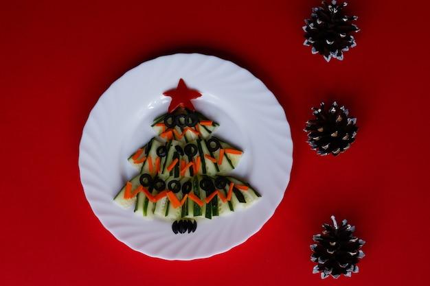コーンと赤の背景にキュウリのサラダで作られた新年の食べ物のクリスマスツリー