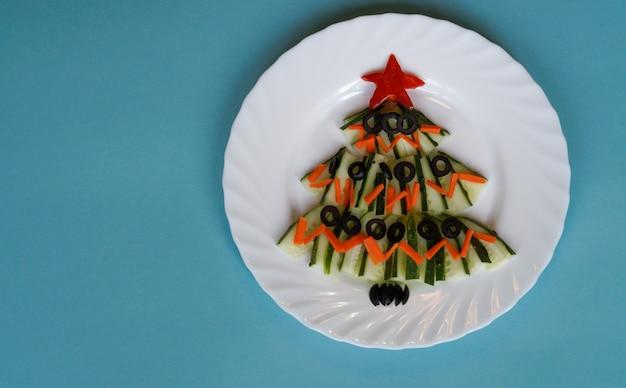 青い背景のクローズアップのテーブルの上のキュウリの新年の食べ物クリスマスツリー