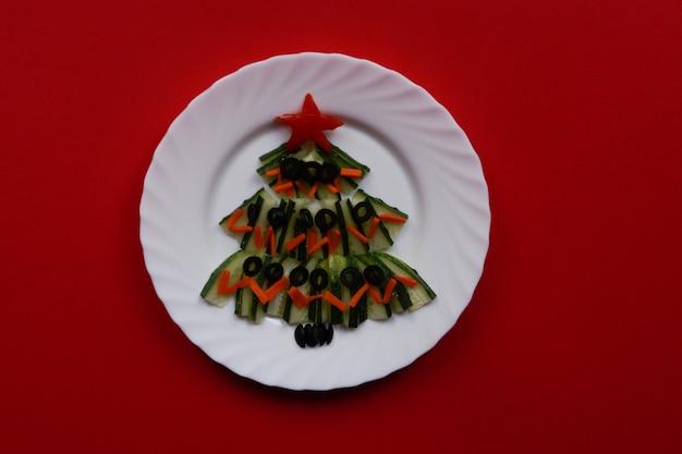 新年の食べ物..赤い背景のクローズアップのテーブル上のキュウリのクリスマスツリー。