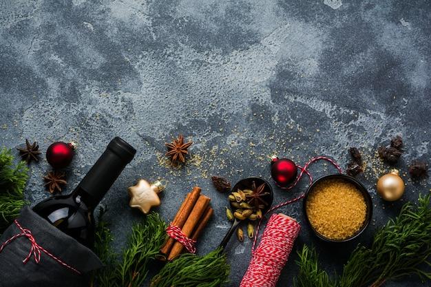 お正月の食べ物の表面。赤ワイン、オレンジ、サトウキビ、スパイスのクリスマスグリューワインボトルを作るための材料。