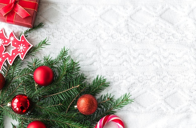 新年のフレームモックアップ。白いニットの背景に松ぼっくり、モミの枝、クリスマスボール