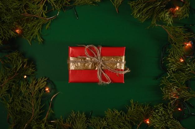 Новогодний подарок на темно-зеленом фоне рождества.