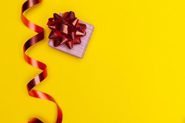 Место для новогоднего подарка для настоящего списка подарочная коробка с красным бантом на желтом фоне