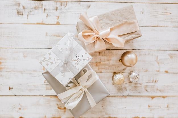 Новогодние подарки и елочные игрушки на деревянном полу