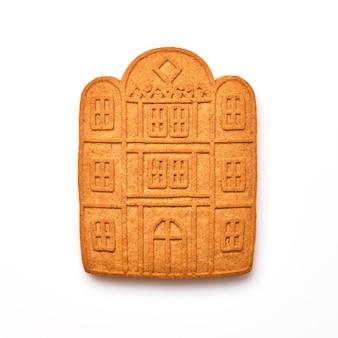 新年のジンジャーブレッドまたは自家製のジンジャーブレッドハウスは、白で隔離された形のクッキーです。
