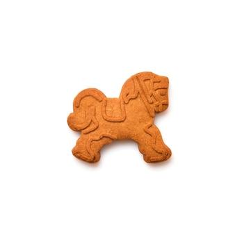 白で隔離される新年のジンジャーブレッドまたは馬のおもちゃの形をしたクッキー。