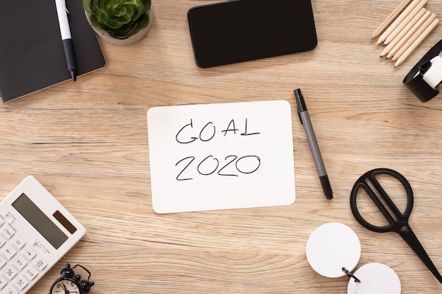 New year goal 2020 on paper top view at wood office table with stationery stuff