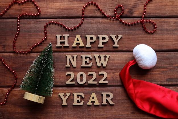小さなクリスマスツリーと新年の帽子と新年のグリーティングカードの碑文明けましておめでとうございます