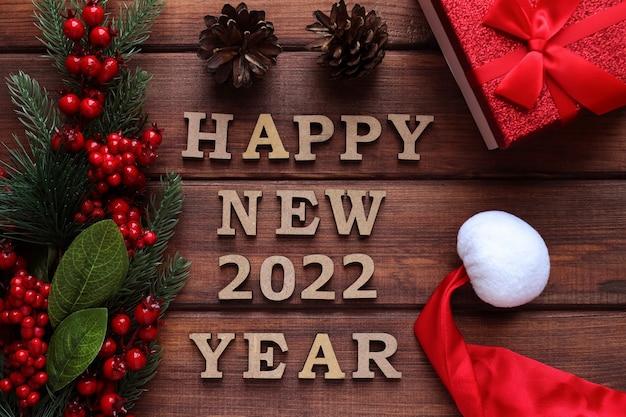 新年のグリーティングカードの碑文トウヒの枝の松ぼっくりとギフトボックスと新年あけましておめでとうございます