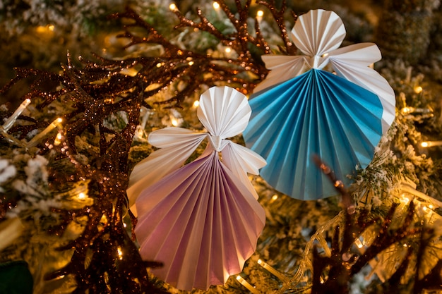 New year handmade angel papercraft origami figures on christmas tree with holiday interior decorations with warm lights. christmas art concept winter card studio shot close-up