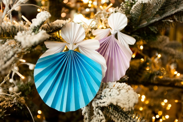 New year handmade angel papercraft origami figures on christmas tree with holiday interior decorations with warm lights. christmas concept winter card studio shot close-up