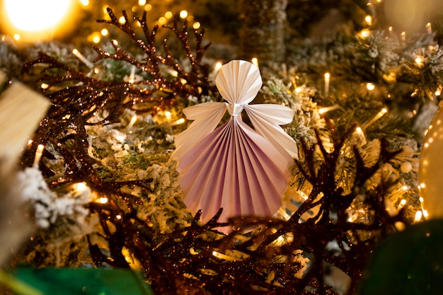 New year handmade angel papercraft origami figures on christmas tree with holiday interior decorations with warm lights. winter card studio shot close-up