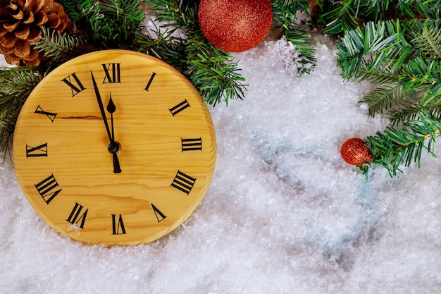 New year happy holidays background with fir tree with snow countdown to midnight clock