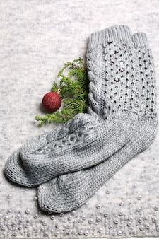 Новогодний праздник фон. вязаные носки, елочная игрушка и еловая ветка на вязаном сером фоне. новогодняя композиция
