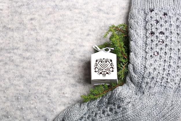 年末年始の背景。ニットの靴下、クリスマスツリーのおもちゃ、ニットの灰色の背景にトウヒの枝。クリスマス作曲