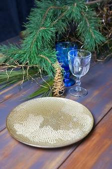 年末年始は金色のプレートでテーブルを飾りました。クリスマスツリーとヴィンテージの青いテーブルの上のヴィンテージワイングラス。