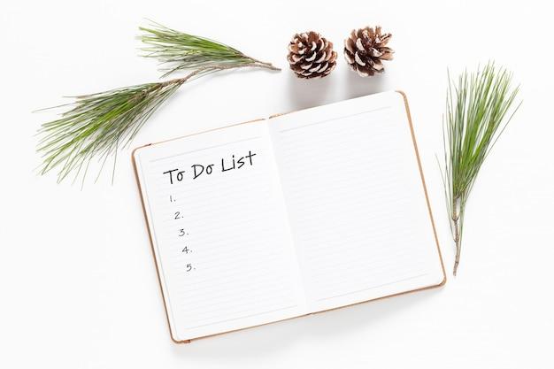 Новый год. праздничные украшения и блокнот со списком желаний на белом столе, плоский стиль. концепция планирования. плоская планировка.