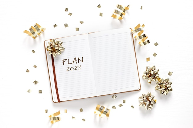 Новый год. праздничные украшения и блокнот со списком желаний на белом столе, плоский стиль. концепция планирования.