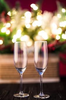 年末年始またはクリスマスの緑の背景。金色のライト、花輪、おもちゃ、空のシャンパングラスで飾られたクリスマスツリーの枝。夜のイルミネーション。新年の挨拶の概念