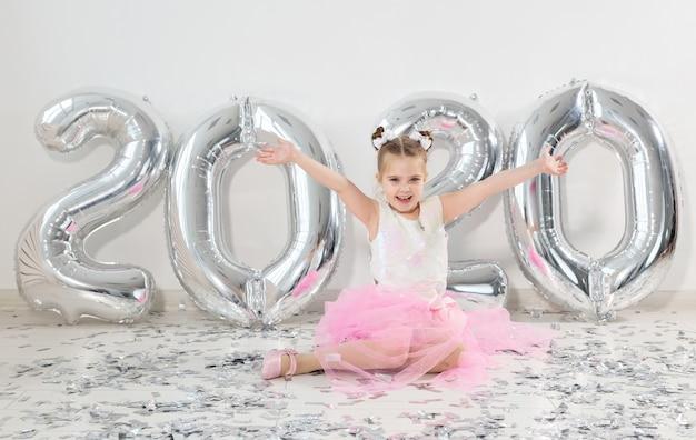 Новый год, праздники и концепция праздника - маленькая девочка сидит рядом с номерами воздушных шаров 2020