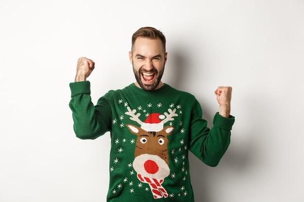 新年、祝日、お祝い。クリスマスセーターで興奮したひげを生やした男、拳ポンプを作り、喜びのために叫び、喜びと勝利、白い背景。