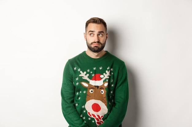 新年、祝日、お祝い。セーターを着た暗いひげを生やした男、優柔不断に見え、脇を見て、白い背景に立っている