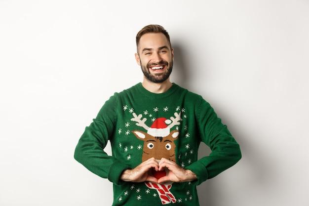 新年、祝日、お祝い。ハートのサインを示し、愛とケアを表現し、白い背景の上に立って、クリスマスセーターの幸せなひげを生やした男