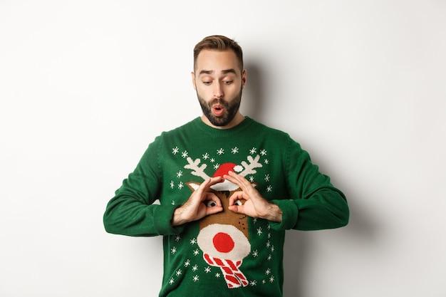 新年、祝日、お祝い。彼のセーターをからかって笑って、白い背景の上に立って、クリスマスパーティーで浮気して幸せな若い男